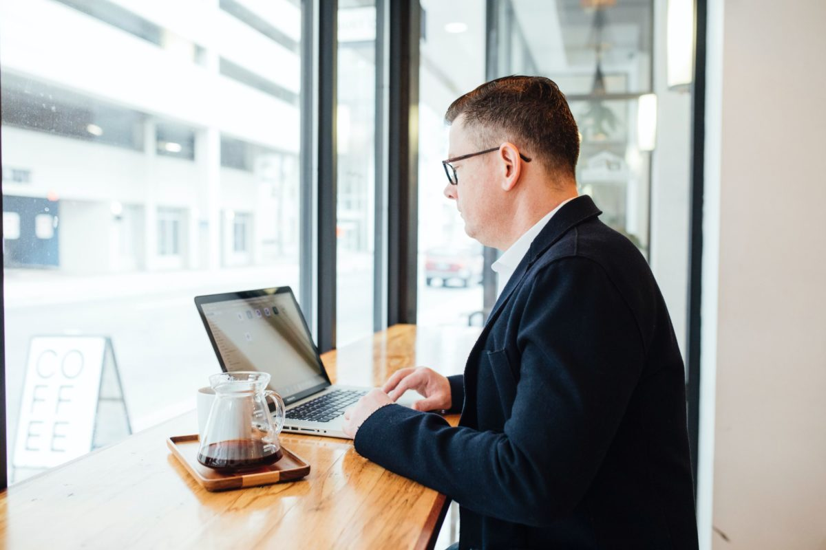 Man in sport coat with glasses, looking at laptop computer in coffee shop