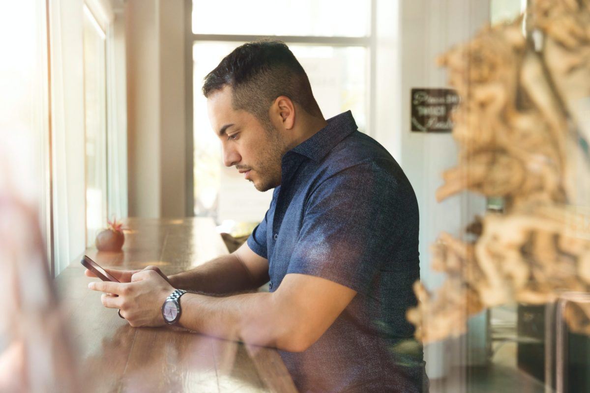 Man in polo shirt looking at mobile phone in coffee shop